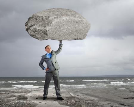 頭の上に巨大な石を保持している強力な実業家
