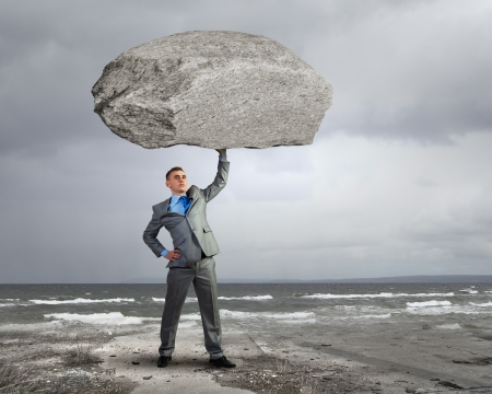 Powerful businessman holding huge stone above head Stock Photo