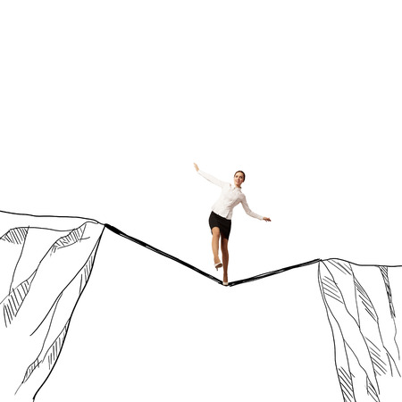 Young businesswoman walking on rope above mountain gap Stock Photo