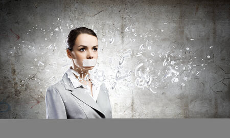 speechless: Young speechless businesswoman with adhesive tape on mouth Stock Photo