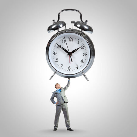 Young strong businessman lifting huge alarm clock above head