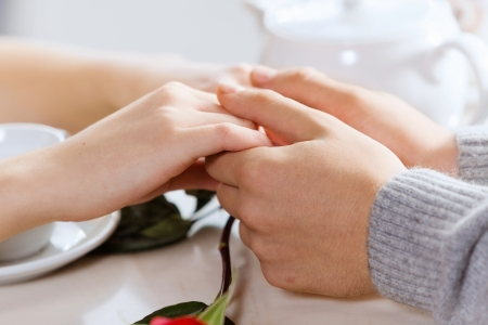 holding close: Close up image of young couple holding hands having date at cafe