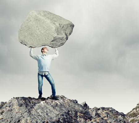 oppressed: Young strong man holding huge stone above head