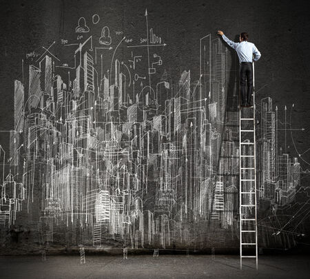 Rear view of businessman standing on ladder and drawing business sketch on wall photo