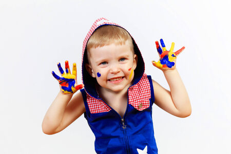 little child with hands painted in colorful paints ready for hand prints photo