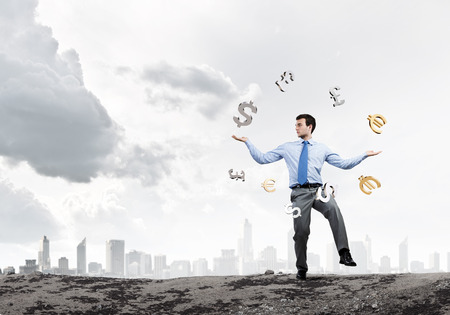 Young businessman juggling with currency symbols against city background photo