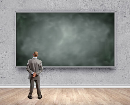 Rear view of businessman looking at chalkboard photo