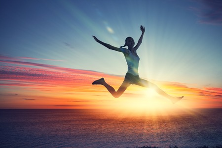 success concept: Silhouette of dancer jumping against city in lights of sunrise Stock Photo