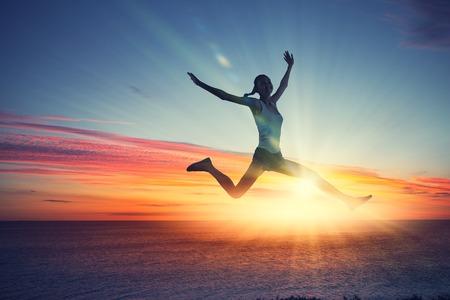bailarina: Silueta del bailar�n que salta contra la ciudad de las luces de la salida del sol Foto de archivo