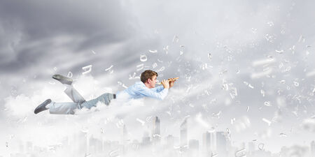 fife: Young businessman flying in sky and playing fife Stock Photo