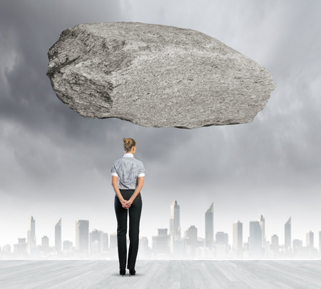 determinism: Rear view of businesswoman looking at urban scene with huge stone above Stock Photo