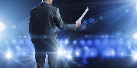 hablar en publico: Vista posterior de altavoz de negocios de pie en el podio en las luces