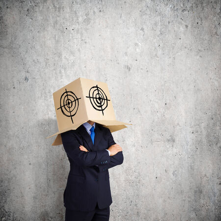Businessman with box on head expressing emotions photo