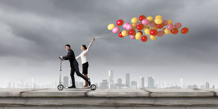 Young businessman and businesswoman riding scooter on roof of building photo