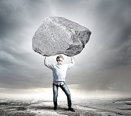 Young strong man holding huge stone above head photo