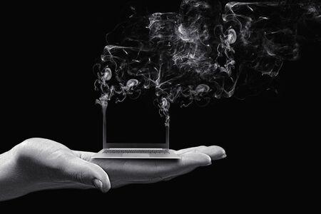 defective: Human hand holding burning laptop on palm