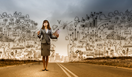 Businesswoman drawing business plan standing on road photo