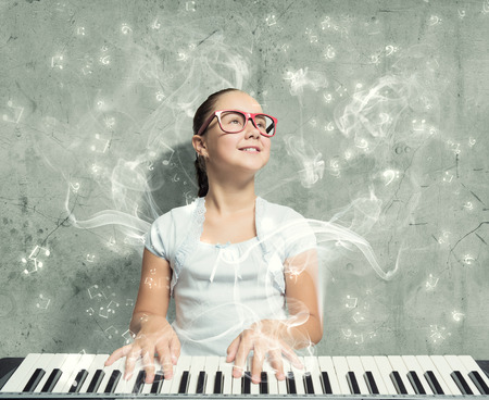 funny glasses: Pretty school girl in funny glasses playing piano