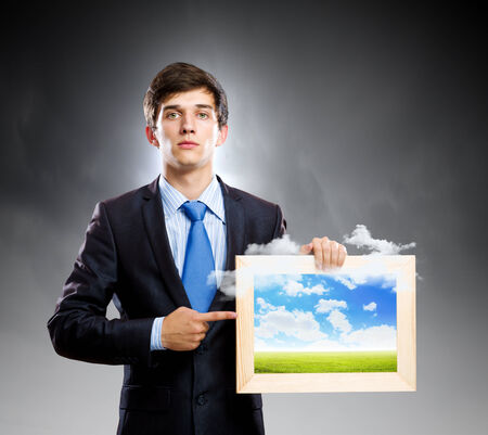 pollution free: Handsome young man holding frame with pictures