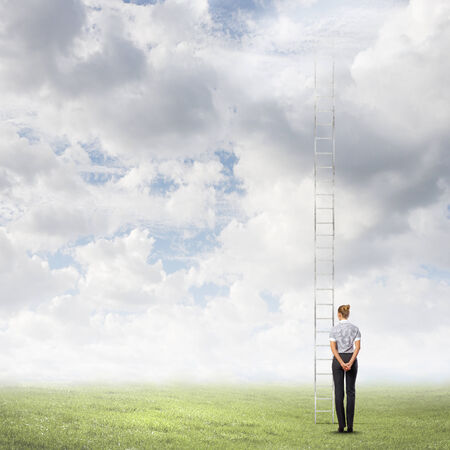 goal oriented: Businesswoman standing with back near long ladder to sky
