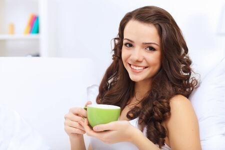 mujer tomando cafe: Retrato de mujer joven y hermosa con la taza de té en casa Foto de archivo