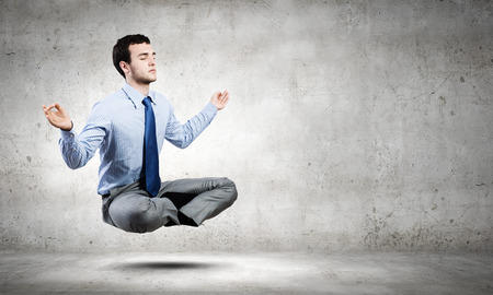 Young businessman sitting in lotus pose and meditating