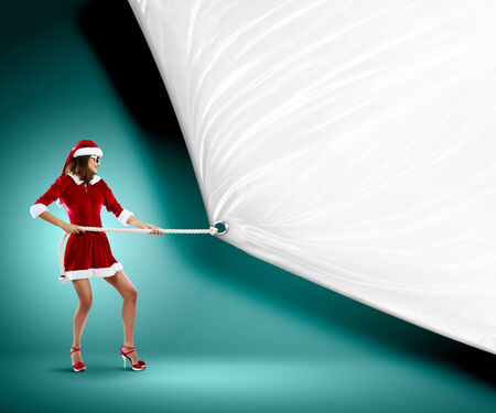 Girl in Santa costume pulling white blank banner  Place for text photo