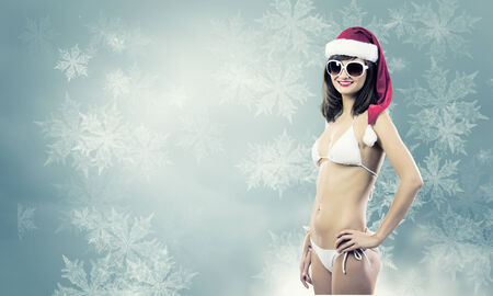 Attractive girl in Santa hat and white bikini against color background photo