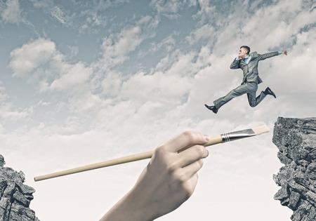 taking risks: Young businessman jumping over gap  Risk concept Stock Photo