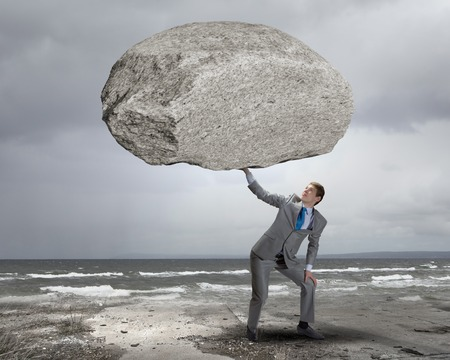hard work: Powerful businessman holding huge stone above head Stock Photo