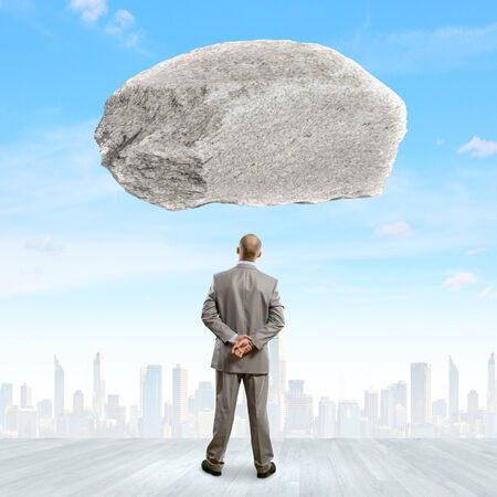 determinism: Rear view of confident businessman with huge stone above