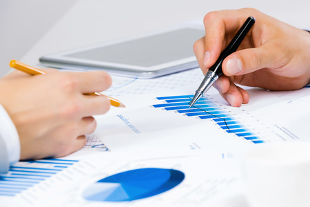 negotiation business: Close up of human hands and documents with graphs and diagrams Stock Photo