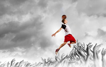 basketball net: Young man basketball player with ball in hands jumping high