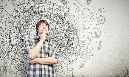 Giovane uomo bello riflessivo nel pensiero casuale sopra le idee Archivio Fotografico - 25644971