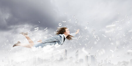 Young pretty businesswoman flying in blue sky photo