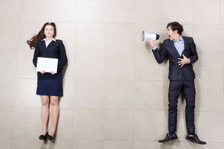 scold: Angry businessman shouting in megaphone on his colleague