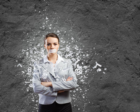 Young speechless businesswoman with adhesive tape on mouth Stock Photo
