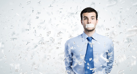 silenced: Young handsome businessman with adhesive tape on mouth Stock Photo