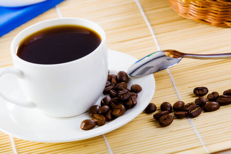 Cup of coffee on saucer with tea spoon and grain photo