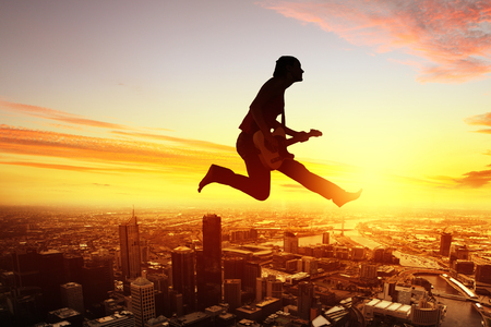 Silhouette of dancer jumping against city in lights of sunrise Stock Photo - 25667560