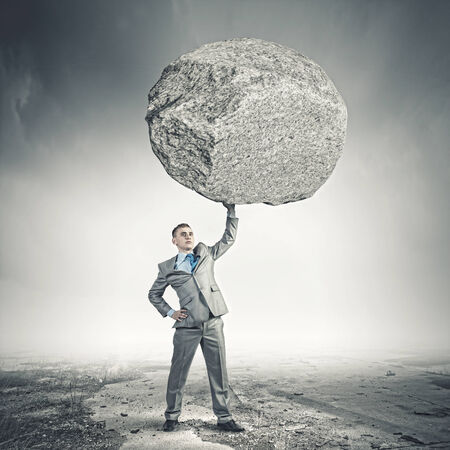Powerful businessman holding huge stone above head photo