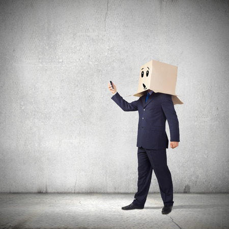 unknown gender: Troubled businessman with carton box on head expressing emotions