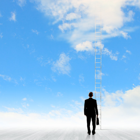 corporate ladder: Back view of businessman standing near long ladder to sky