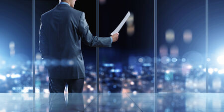 inside technology: Businessman standing against office window reading documents