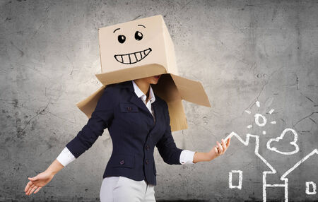 cowardice: Conceptual image of businesswoman with carton box on head Stock Photo