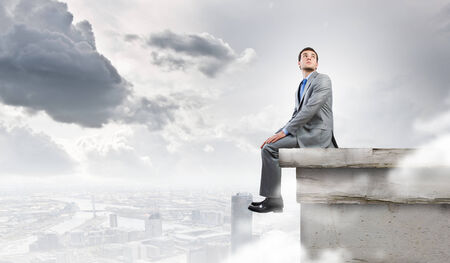 Young handsome businessman sitting at the edge of building roof photo