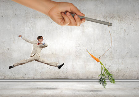 chased: Funny image of businessman chased with carrot