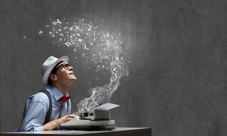 Jonge grappige man in glazen schrijven op schrijfmachine