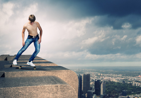 Skater in jeans riding on top of building photo