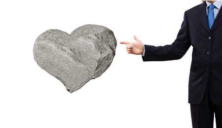 prudent: Businessman pointing at stone in shape of heart Stock Photo